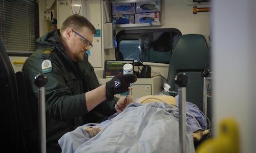 A paramedic using a robotic glove in a 5G ambulance